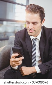 Close-up of handsome businessman using mobile phone in office