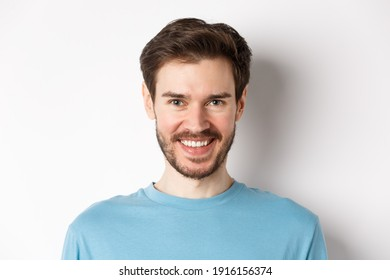 Close-up of handsome caucasian man smiling with white teeth, looking confident at camera, standing in blue shirt on white background