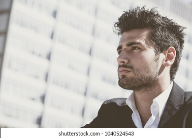 Close-up of a handsome and charming young man with stylish haircut. Beard and intense look. Behind him the windows of a large building.