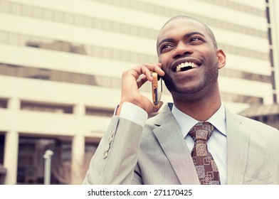 Closeup handsome happy laughing young businessman talking on mobile phone outdoors. Instagram filter effect