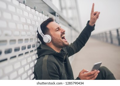Closeup of a handsome man sitting on the ground with headphones singing while listening music and holding phone.
