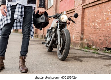 Close-up of a handsome rider biker guy hand with black helmet in front of classic style cafe racer motorcycle. Bike custom made in vintage garage. Brutal fun urban lifestyle. Outdoor portrait.