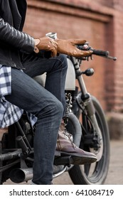 Closeup of a handsome rider biker guy hand puts on a leather glove while sit on classic style cafe racer motorcycle. Bike custom made in vintage garage. Brutal fun urban lifestyle. Outdoor portrait.