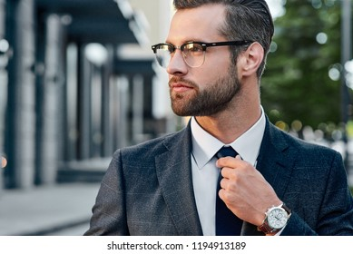 Close-up handsome and successful man in spectacles and in an expensive suit. He is in a white shirt with a tie. The man straightens his tie, his face unshaven.