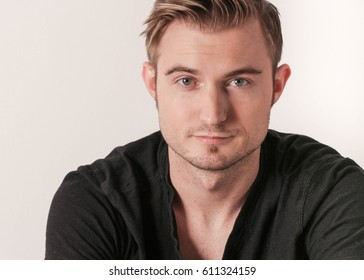 close-up of a handsome white Caucasian man portrait. attractive young man in black shirt posing in studio with stylish look. The man has a sexy hair style.