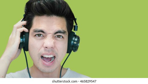 Close-up Handsome young asian man looking happy listening to music on his headphones isolated on green background.Copy space. Human Face.
