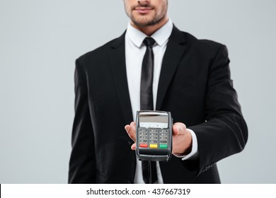Closeup of handsome young businessman giving you payment terminal