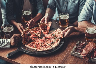 Close-up of handsome young friends drinks beer and eating pizza at pub.