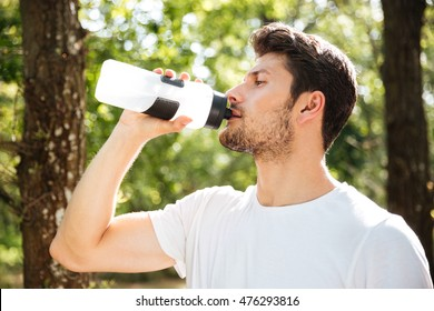 Closeup of handsome young man athlete drinking water in forest