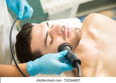 Closeup of a handsome young man getting facial rejuvenation therapy in a health spa