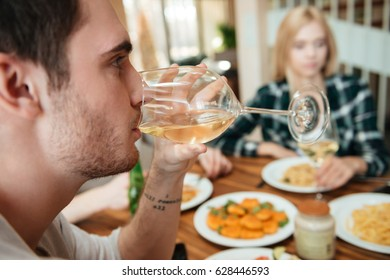 Closeup of handsome young man having dinner and drinking wine with friends on the kitchen