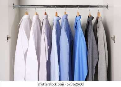 Closeup of hangers with different shirts in wardrobe