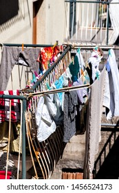 Closeup of hanging clothes in summer drying on rack clothesline line in Montepulciano old vintage Italian Italy apartment building in town village