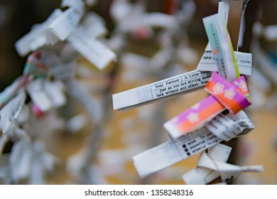 close-up hanging tied of omikuji, or Japanese fortune paper, are wrapped on string at Japanese temple