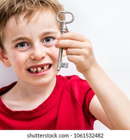 close-up of a happy 7-year old blue eye-boy showing a key for fun tooth fairy, growing up pride or solution to child healthcare