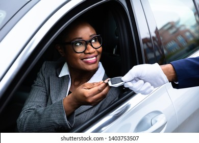 Close-up Of Happy African Businesswoman Sitting Inside Car Giving Car Key To Valet
