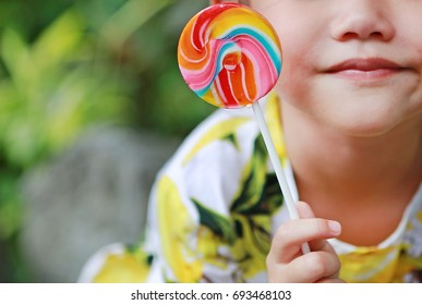 Close-up happy asian little girl with lollipop candy with copy space.