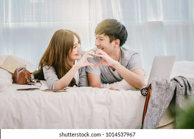 Closeup Happy Asian Lover or couple in love with doing heart form hand action on the bed in bed room at modern home, boyfriend pointing to the mobile phone, Lover and life style concept,