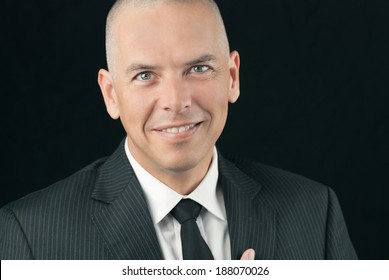 Close-up of a happy bald man smiling to camera.