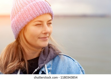 Closeup of happy beautiful young woman in blue knitted hat and denim coat, smiling, posing, outdoors on sunny autumn day.