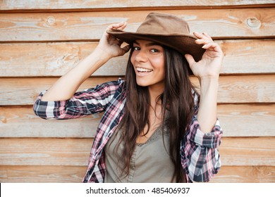 Closeup of happy beautiful young woman cowgirl in hat over wooden background