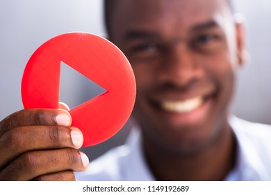 Close-up Of Happy Businessman Holding Red Play Button