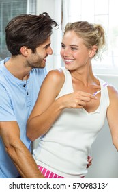 Close-up of happy couple hugging while brushing teeth in bathroom