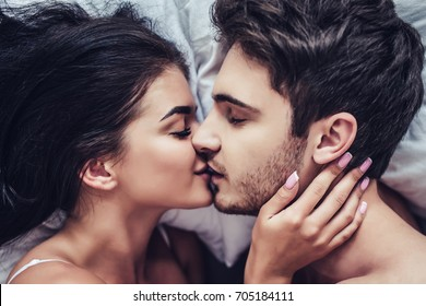 Close-up of happy couple is lying in bed together. Kissing and enjoying the company of each other.