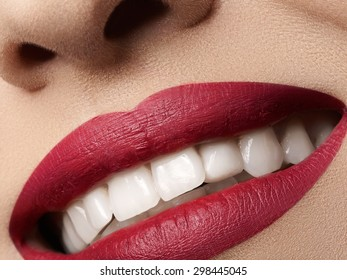 Close-up happy female smile with healthy white teeth, bright magenta lips make-up. Cosmetology, dentistry and beauty care. Macro of woman's smiling mouth. Beautiful smile