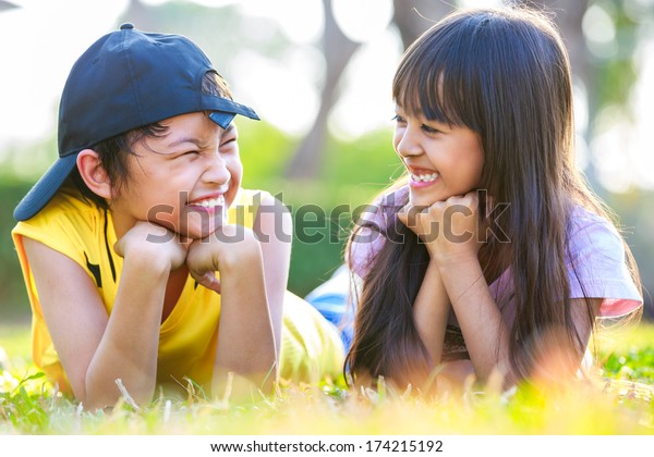 Closeup happy little asian girl with his brother laying on green grass