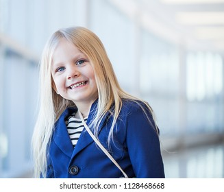 Close-up of happy little girl wearing dress and blue jacket