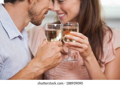 Close-up of a happy loving young couple toasting wine glasses