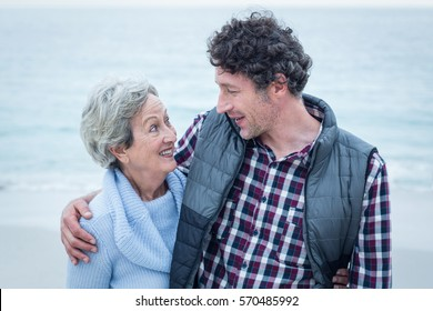 Close-up of happy man standing with mother at sea shore