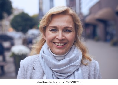Closeup of happy mature woman walking on the street, posing at camera
