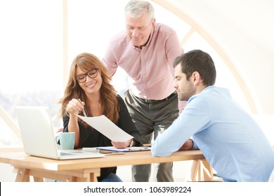 Close-up of happy middle aged businesswoman consulting with senior manager and young assistant while sitting at office desk and working together on new project. Teamwork.
