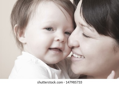 Closeup of happy mother caressing baby girl over colored background