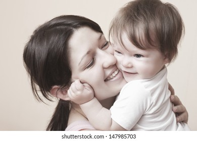 Closeup of happy mother hugging baby girl over colored background