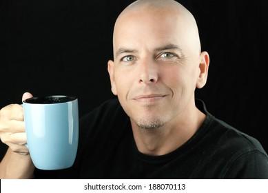 Close-up of a happy, peaceful bald man lifting his mug to camera.