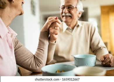Close-up of happy senior couple holding hands while talking at dining table.