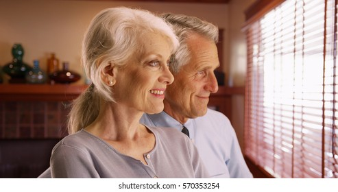 Closeup of happy senior couple looking out the window