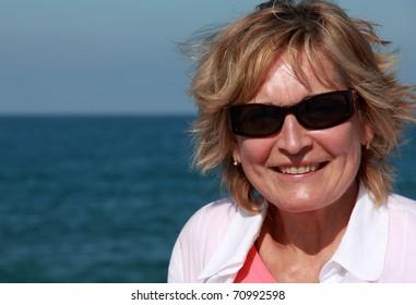 closeup of happy senior woman on beach