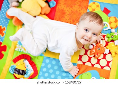 Closeup of happy six months baby boy crawling on colorful playmat