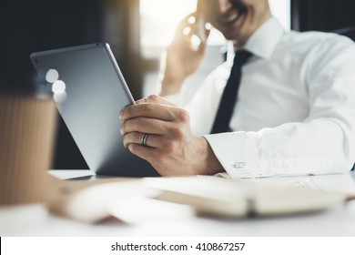 Close-up of happy smiling businessman or employer working on digital tablet and talking on his smartphone in modern office interior, flare light