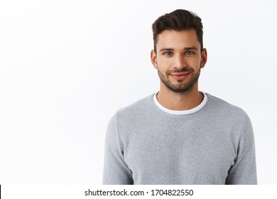 Close-up happy smiling confident macho man with bristle in stylish grey sweater, looking trustworthy and sincere with friendly kind grin, standing white background self-assured and motivated