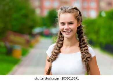 closeup happy st 20- year-old woman in a white T-shirt with two braids in the park