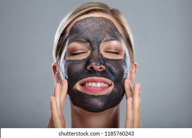 Close-up Of A Happy Woman Using Activated Charcoal Face Mask On Grey Background