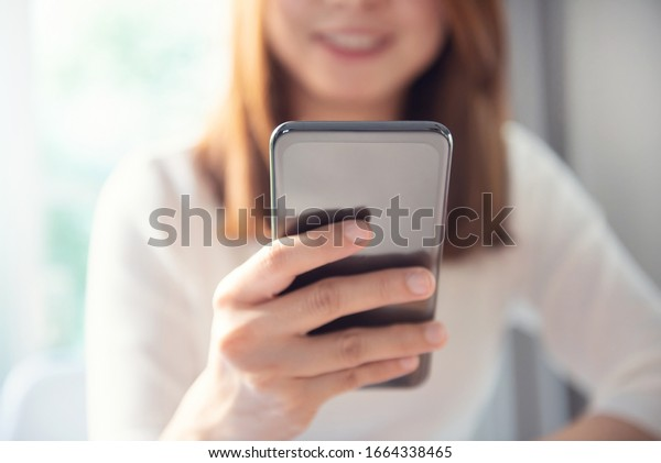Closeup - Happy woman using smartphone at home, She chatting Online Messaging and social network on mobile.