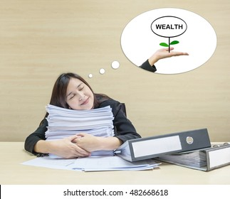 Closeup happy working woman sleeping with happy face with hug work paper in front of her and good dream to have wealth in future in text box on blurred wood desk and wall textured background in room