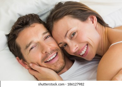 Close-up of a happy young couple lying together in bed at home