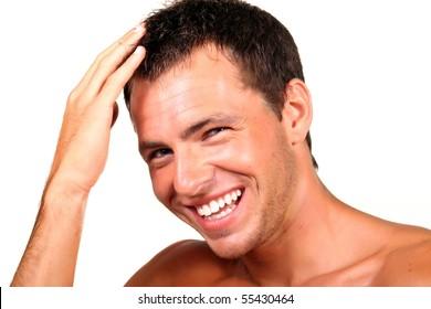 Closeup of a happy young man looking at camera and touching his hair